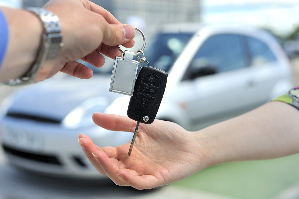 car key being passed from one hand to another in front of a silver car