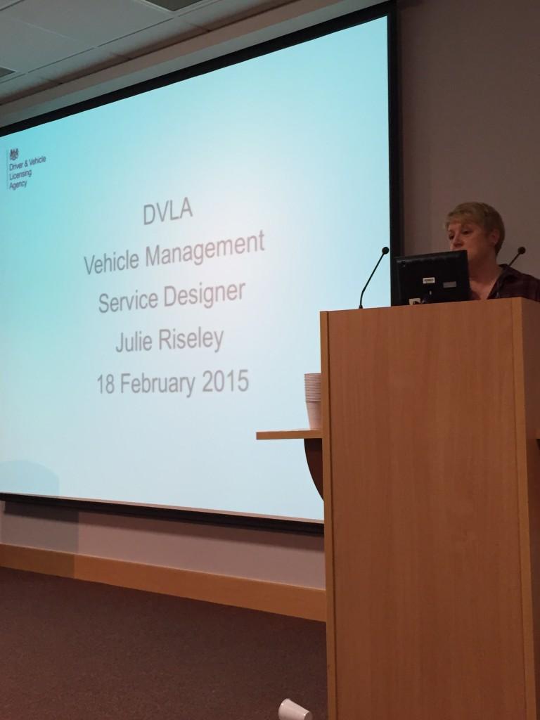 Julie Risley standing behind a lectern delivering a presentation
