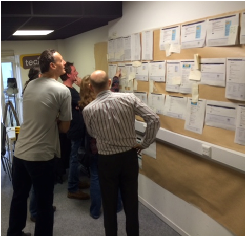 DVLA staff looking at paper copies of each service placed on a wall
