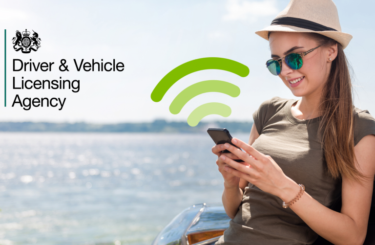 A young woman leaning on her car beside the sea looking at her phone with a wifi symbol coming out of it