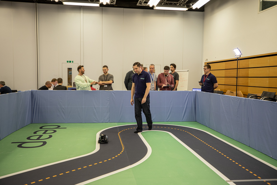 Race track with a man racing a toy car