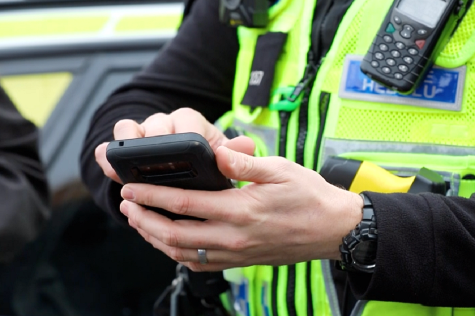 police officer holding mobile device